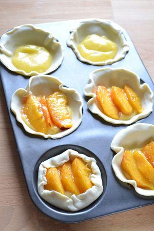 Mettete un dischetto di pasta in ogni stampino, riempitelo con la crema al lime e completate con 3-4 fettine di pesca