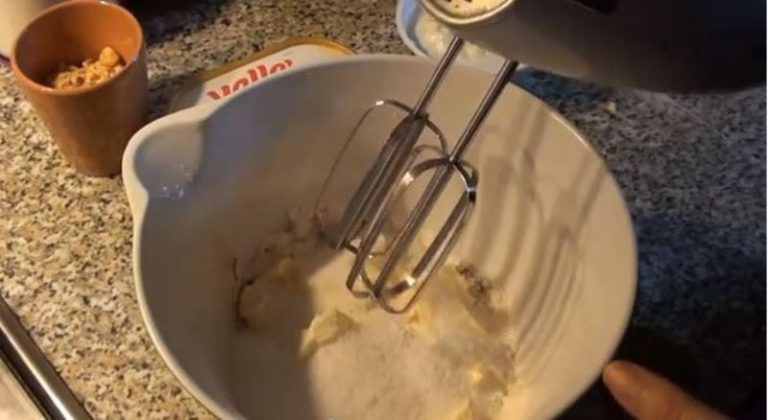 Aggiungete la buccia del limone grattuggiata, gli aromi, lo zucchero e vallè+burro a fiocchetti. Lavorate il composto con le fruste finché non risulti sabbioso.