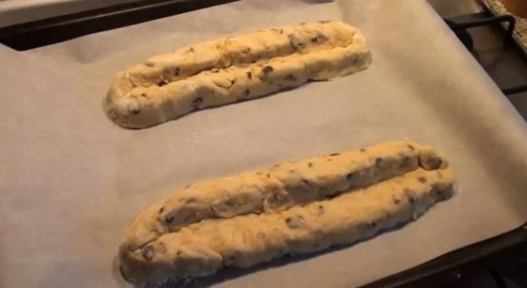 Fate lo stesso con la pasta rimasta. Poggiate gli stollen su una teglia ricoperta di carta forno e infornate a 160 °C per 45 minuti circa o finché i dolci non risulteranno leggermente dorati.