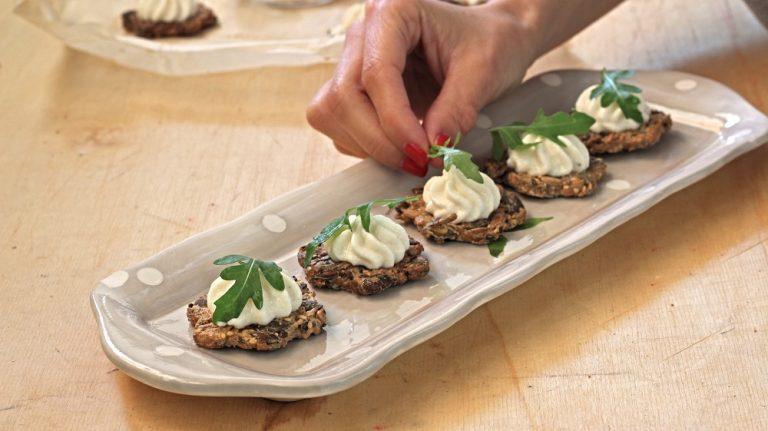 Distribuite la crema sulle basi, usando preferibilmente una tasca da pasticcere, decorate ogni tartina con la rucola, un pizzico di pepe nero e servite.