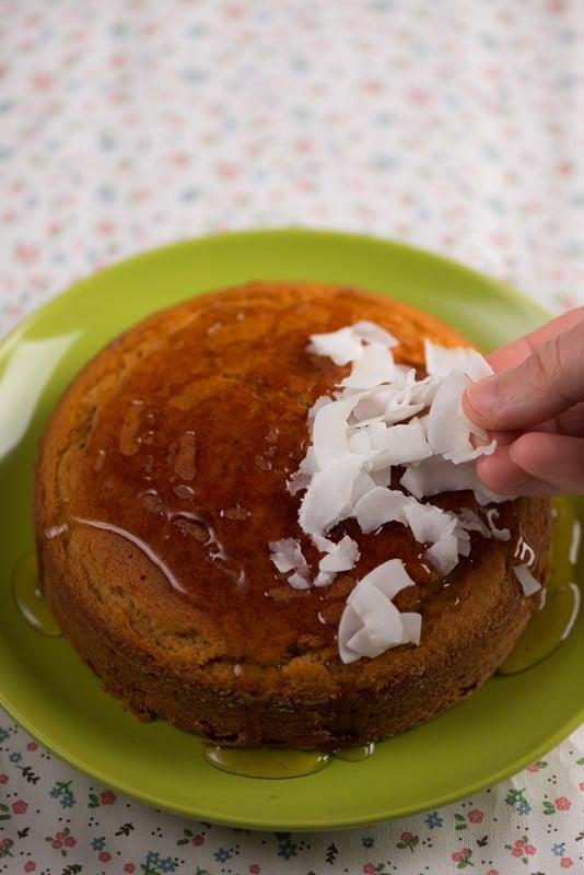 Lasciate raffreddare 5 minuti nella teglia prima di sformarla, poi ponete la torta su una griglia e lasciate che si raffreddi del tutto. Per la decorazione: cospargete la superficie della torta con il miele e distribuitevi sopra le scaglie di cocco.