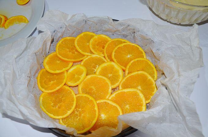 rivestire la teglia con della carta da forno bagnata e strizzata, adagiare l'impasto, versare circa 3 cucchiai di zucchero di canna e le fette d'arancia. Cuocere la torta a 170 ° per 35 min.