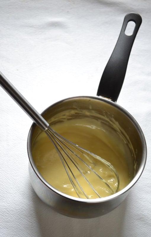 Quando la crema si addensa, spegnete il fuoco e trasferite in una ciotola. Coprite con carta forno o pellicola a diretto contatto con la superficie in modo da non fare formare la pellicina. Lasciate raffreddare del tutto e mettete in frigo