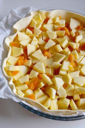 Sbucciate le mele, eliminate il torsolo e tagliatele a pezzetti. Tagliate anche le albicocche. Decidete voi in base al vostro gusto quante metterne. Disponete le mele e le albicocche sulla base di crema