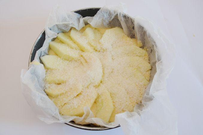 In una teglia rivestita di carta forno bagnata e strizzata versare metà dell'impasto e metà delle mele tagliate. Aggiungere quindi il restante impasto e decorare con le mele restanti ed il cocco.