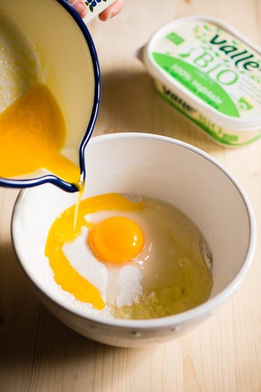 Preriscaldate il forno a 180°.<br /> Ungete uno stampo rotondo e cospargetelo con zucchero semolato.<br /> In una ciotola o in un frullatore mettete la farina, lo zucchero, le uova, la margarina fusa e intiepidita, il latte, un pizzico di sale e i semi  di vaniglia