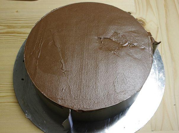 Prendere la torta dal frigo, bagnare la genoise quindi coprire con la mousse al cioccolato fino al bordo. Se ne avanza niente paura, mettetela nelle ciotoline e mangiatela da sola o con delle fragole.