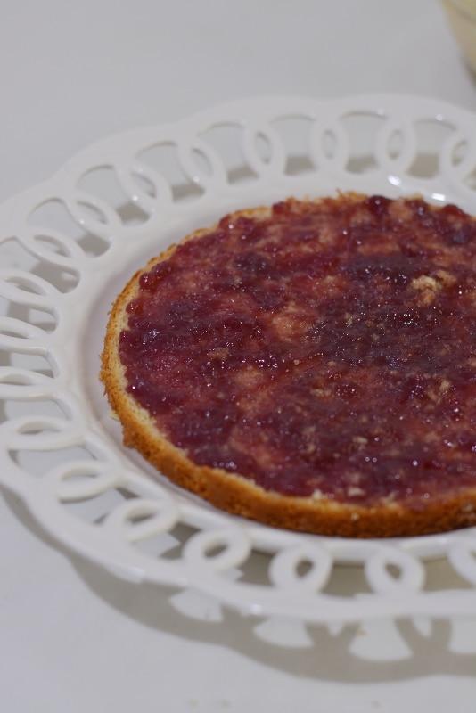 tagliare in 3 parti il pan di spagna e farcire la base con uno strato di confettura di lamponi
