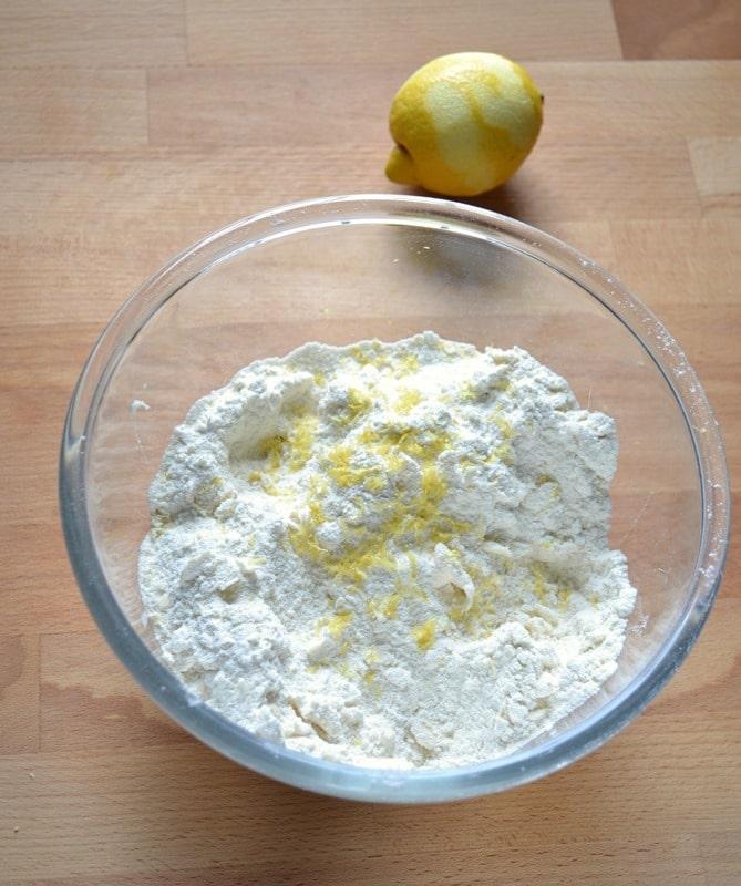 Accendete il forno a 180 gradi; preparate una placca rivestita con carta forno. Versate la farina in una ciotola capiente, unite lo zucchero semolato, il lievito e mescolate. Aggiungete la Vallé+Burro fredda  a pezzetti e lavorate gli ingredienti strofinandoli tra i polpastrelli fino a ottenere un composto simile a grosse briciole. Lavorate in fretta e senza far scaldare troppo la Vallé. Aggiungete la scorza di limone grattugiata.