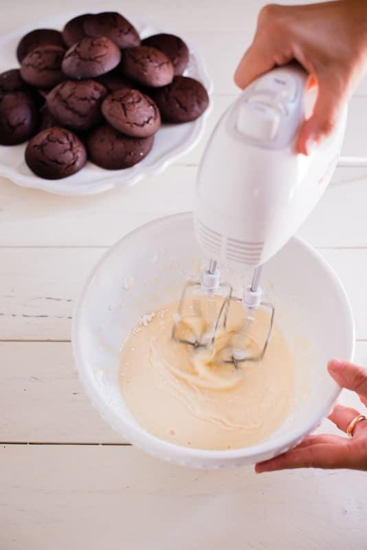 Preparate la farcitura: montate la panna e lavorate con una frusta elettrica il formaggio cremoso con lo zucchero a velo,