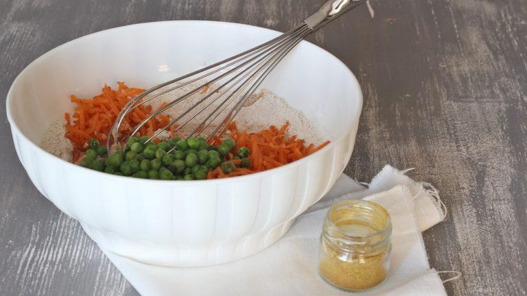 Mescolate leggermente con una frusta e unite anche carote, piselli e curry in polvere secondo gusto. Mescolate ancora con la frusta quel tanto che basta per ottenere un composto omogeneo.