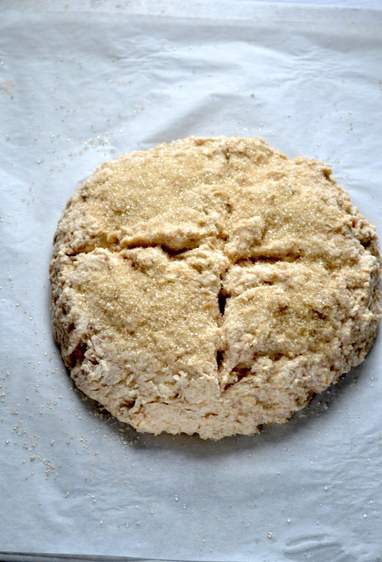 Versate l'impasto sulla leccarda e formate una pagnotta tonda. Incidete e croce, distribuite lo zucchero rimasto sulla parte superiore e infornate per 40 minuti circa (o fino a quando il pane è colorito sotto).