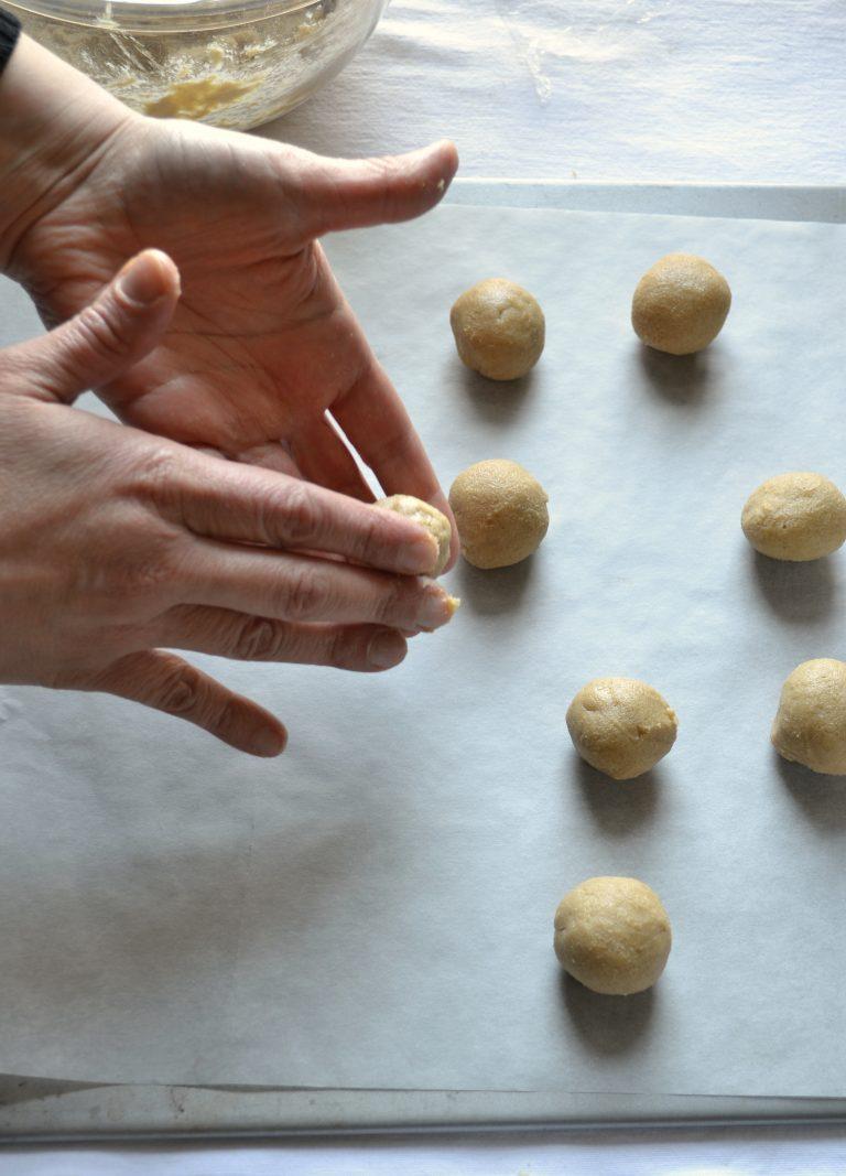 Trascorso il tempo di riposo, accendete il forno a 180 gradi. Foderate una leccarda con carta forno. Formate tante palline grandi all'incirca come noci e appoggiatele, ben distanziate, sulla leccarda.