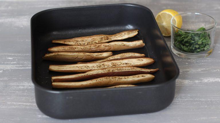 Lavate le melanzane e tagliatele a spicchi lunghi e sottili. Adagiatele in una teglia da forno, salatele leggermente e fatele arrostire in forno a 160°C per 20 minuti.