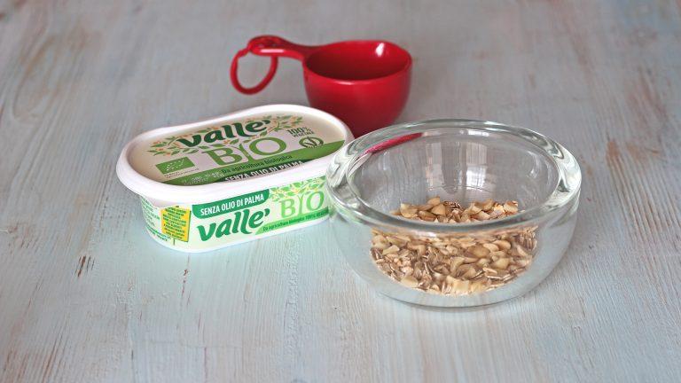 Tritate le mandorle ed unitele in una ciotola con i fiocchi d'avena, il pizzico di sale e cannella a piacere.