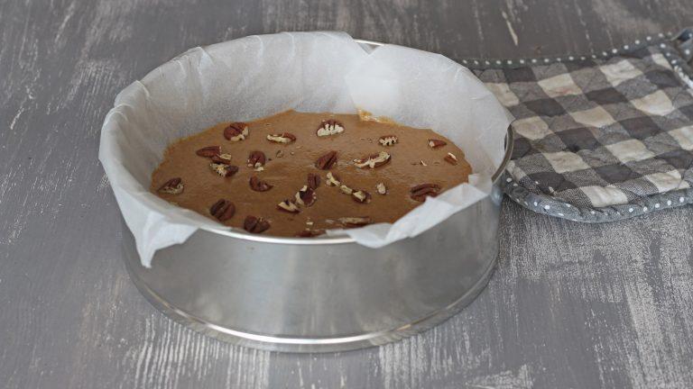 Versate l'impasto in uno stampo a cerniera di 22-24cm di diametro, cospargete la superficie della torta con le noci e cuocetela in forno a 160∞C per 45 minuti.