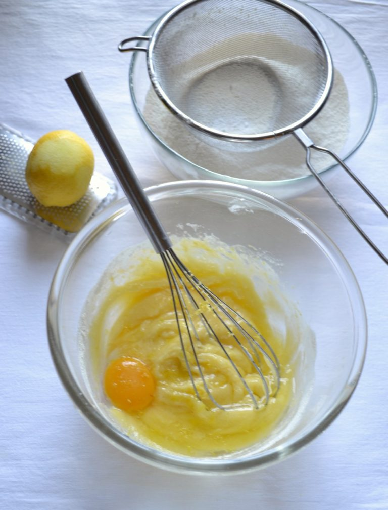 Accendete il forno a 180 gradi. ungete e infarinate uno stampo a cerchio rimovibile (diametro 20 cm).  Mescolate farina e lievito e setacciate. In un'altra ciotola, lavorate la Vallé Omega3 con 100 gr di zucchero fino a ottenere un composto cremoso. Unite un uovo alla volta, mescolando bene e aggiungendo la scorza grattugiata di limone tra uno e l'altro.