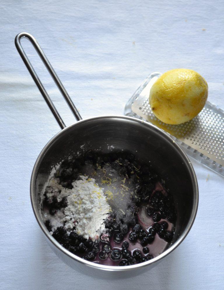 Mentre la torta si raffredda, procedete con la farcitura. Versate i mirtilli in un pentolino dal fondo pesante, poi aggiungete lo zucchero semolato, l'amido di mais, la scorza e il succo del limone, 3-4 cucchiai di acqua e mescolate. Mettete a cuocere a fuoco medio. Appena il composto inizia a bollire, abbassate il fuoco e lasciate addensare per 2-3 minuti. Spegnete il fuoco.