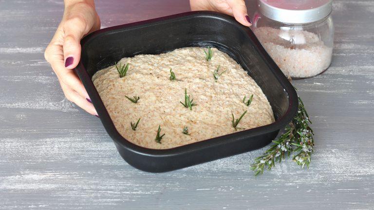 Mettete l'impasto nella teglia rettangolare (o metà in ogni teglia quadrata), pennellate la superficie con l'olio e completate con rosmarino e sale grosso a piacere.