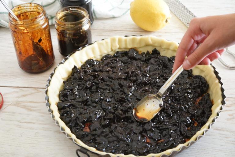 Distribuire la marmellata di ciliege in quantità sufficiente per coprire la base.