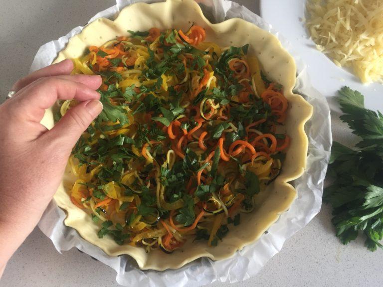 Sistemarla in una teglia  con la sua carta da forno e versare sul fondo le verdure.