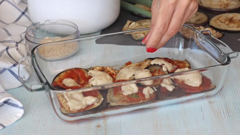 Insaporite la passata di pomodoro con un pizzico di sale e foglie di basilico tritate a piacere. Stendetene un po' sul fondo di una teglia da forno e cominciate a comporre gli strati: melanzane, passata di pomodoro, besciamella e mandorle tritate. Ripetete fino a esaurire gli ingredienti, finendo con le mandorle tritate (il