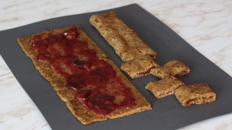 Dividete l'impasto in due rettangoli per il lungo e spalmate su ognuno metà del ripieno di marmellata. Chiudete ogni rettangolo come a formare uno strudel e tagliatelo a pezzi larghi 2cm circa per ottenere i biscotti.