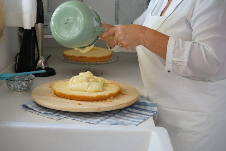 Far raffreddare. Tagliare la torta a metà nel senso della lunghezza. Con la bagna ottenuta mescolando acqua, zucchero e liquore, spennellare entrambi i dischi.<br /> Versare sulla base tutta la crema pasticciera e distribuitela uniformemente fino al bordo.<br />