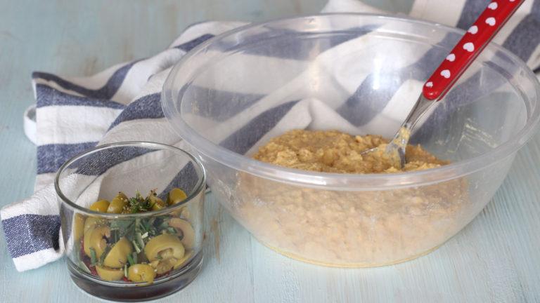 Aggiungete all'impasto i pomodori secchi e le olive tritate, l'aglio, le erbe aromatiche sminuzzate, pepe a piacere e per ultimo il lievito. Mescolate per incorporare il tutto in modo uniforme.
