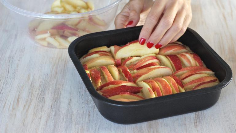 Versate l'impasto nello stampo preparato in precedenza, decorate con le fettine di mela e cuocete in forno preriscaldato a 180 gradi per 35-40 minuti.
