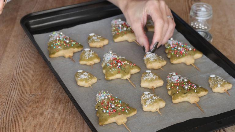 Decorate i biscotti con una glassa preparata mescolando lo sciroppo d'agave con il tè matcha, ricopriteli di zuccherini e di cocco per creare l'effetto neve. Lasciateli asciugare all'aria.
