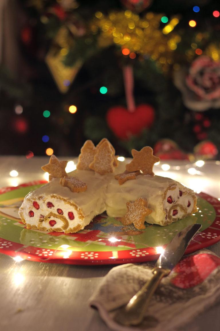 Ricoprite il tronchetto con il frosting e completate la decorazione con i biscotti speziati spolverizzati di zucchero a velo.