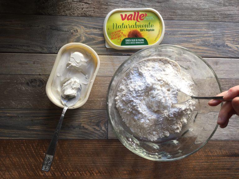 In una ciotola versare la farina, lo zucchero e Vallé Naturalmente e lavorare con la punta delle dita per amalgamare tutti gli ingredienti e raggiungere una consistenza sabbiosa.