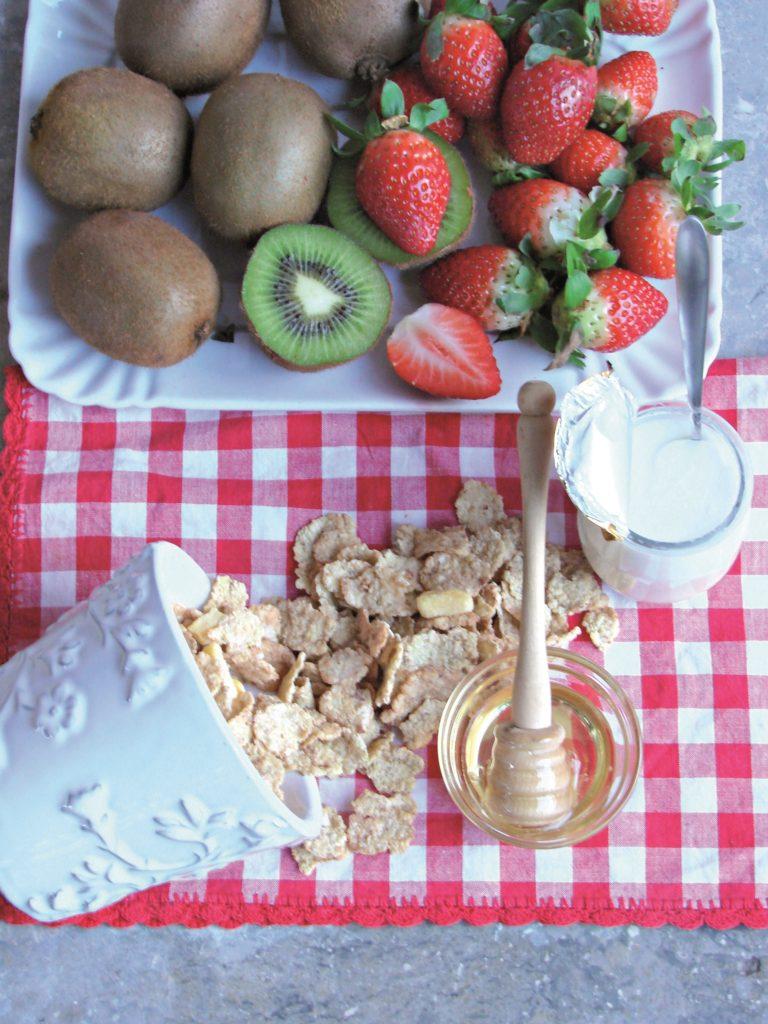 Tagliare a dadini metà delle fragole e un kiwi;<br /> metterli in una ciotola con il miele, i cereali e lo<br /> yogurt, mescolare per amalgamare gli ingredienti