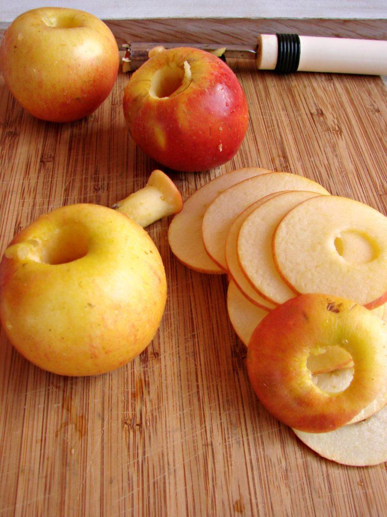Lavare le mele, scegliendo le 3 più grosse, privarle del torsolo con l'apposito attrezzo, affettarle a rondelle sottili e aggiungerle al pollo insieme<br /> alle altre mele intere. A parte, tritare le olive e affettare i pomodori a rondelle dopo aver tolto il solo picciolo, metterli nel tegame con l'acqua rimasta, salare pepare e distribuire il finocchietto tritato.
