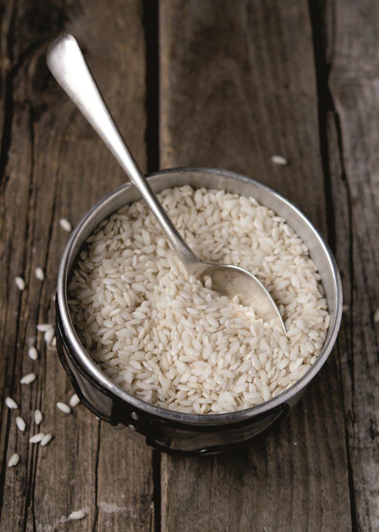 Filtrare il brodo, tenere da parte la foglia di porro e disossare la carne. Tritare finemente la cipolla rimasta. Metterla in una casseruola con un cucchiaio di olio e un cucchiaio<br /> di brodo e farla appassire su fuoco medio. Unire il riso, farlo tostare brevemente e sfumare con il vino rimanente. Versare il brodo caldo e portare il riso a cottura unendo ulteriore brodo se<br /> necessario.