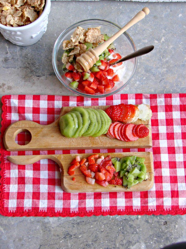 Affettare finemente la frutta rimasta e comporre<br /> i bicchieri distribuendo metà composto al miele,<br /> uno strato di kiwi e uno di fragole a fette, finire<br /> ricomponendo l'alternanza, il composto al miele, i<br /> kiwi e le fragole a fette.