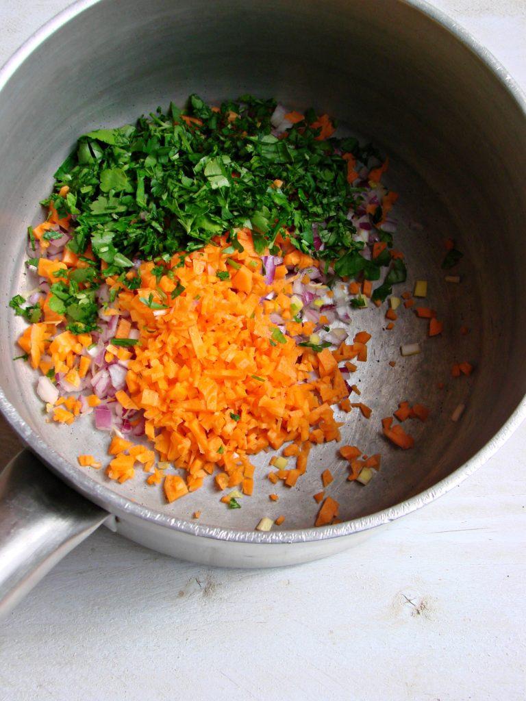 Tritare la carota, la cipolla e il prezzemolo, riporli in un tegame con 3 cucchiai di olio, soffriggerli per pochi istanti e versare i ceci sciacquati;<br /> coprire con il brodo e cuocere per 2 ore. Recuperare 300 ml di brodo di cottura dei ceci bollente e usarlo per sgranare il cous cous, unire 20 g di<br /> Vallé  Omega3, chiudere con il coperchio e far rinvenire la semola per circa 5 minuti. Unire poi i ceci al cous cous e mescolate.