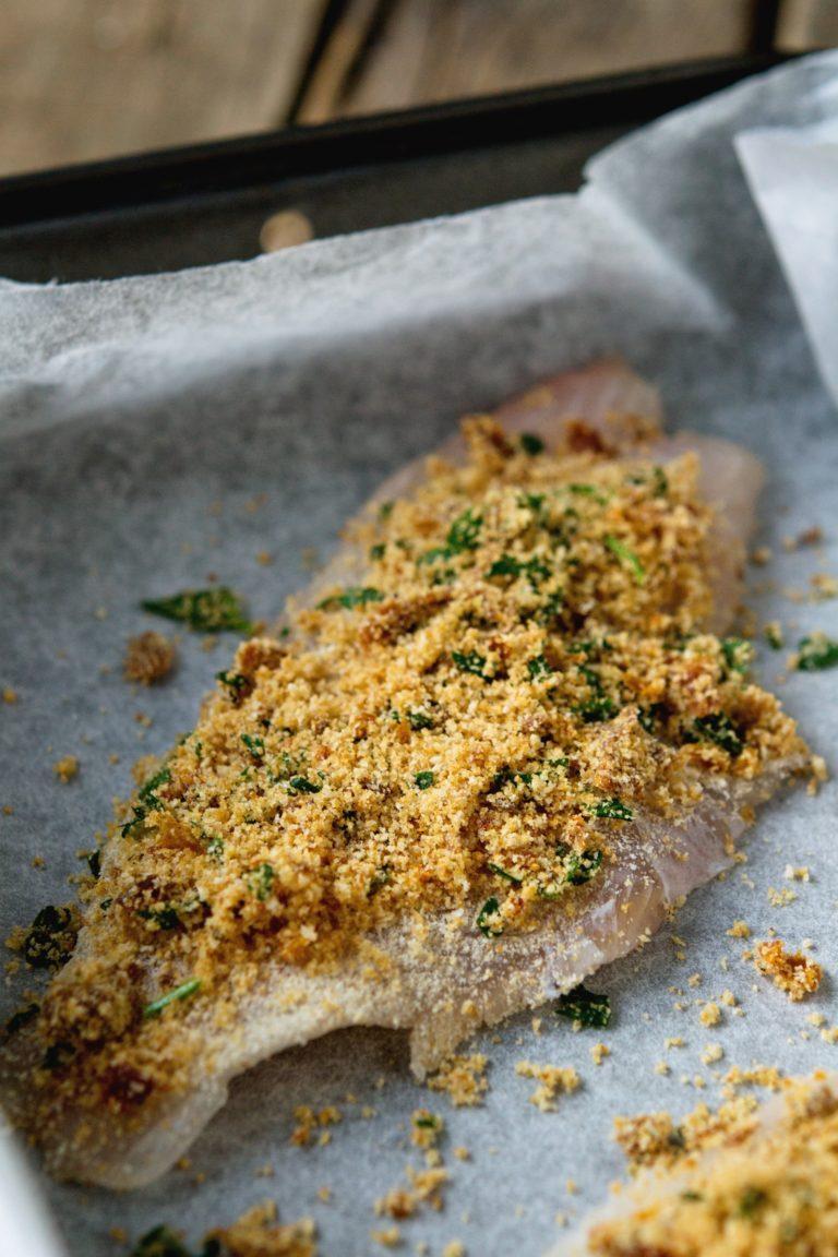 Coprire una teglia con carta da forno e posizionarvi sopra i filetti di pesce. Cospargerli con le briciole di pangrattato e far cuocere in forno caldo a 200° per 12 minuti.