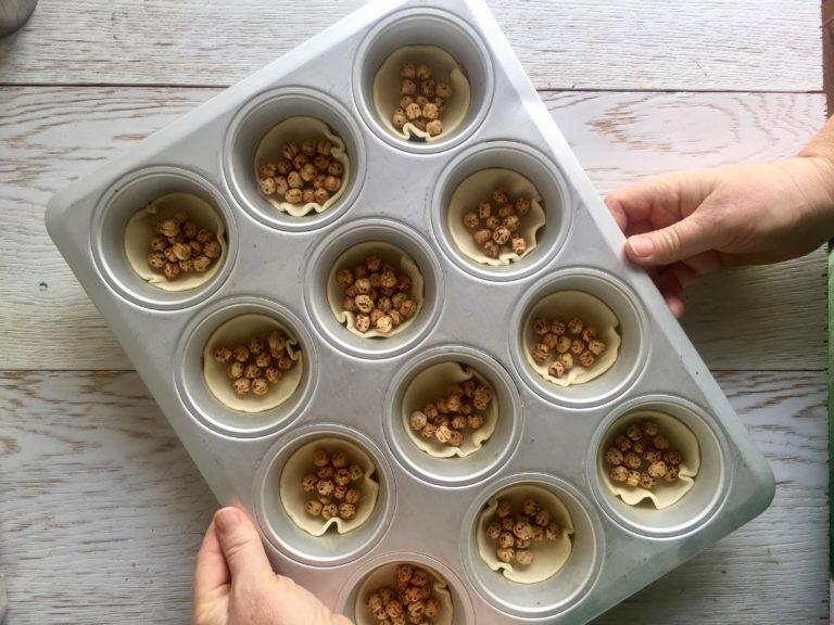 Mettete ogni cerchietto sul fondo della teglia, bucherellatelo con i rebbi di una forchetta e coprite la base con legumi secchi per evitare che si gonfi. Infornare 10 minuti a 180° o finché si colora la sfoglia.