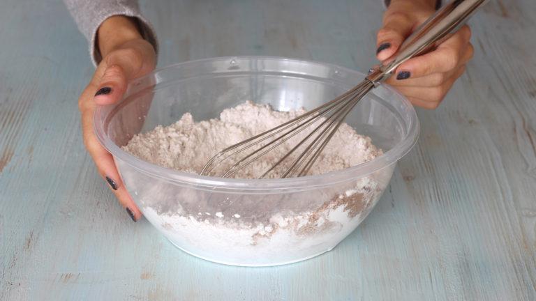 Accendete il forno a 180°C. Mettete in una ciotola la farina, il lievito e lo zucchero di canna e mescolate bene con una frusta.
