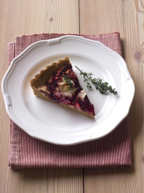 Farcire la torta terminando con i pezzetti di formaggio caprino prima di infornare per 25 minuti a 180°.