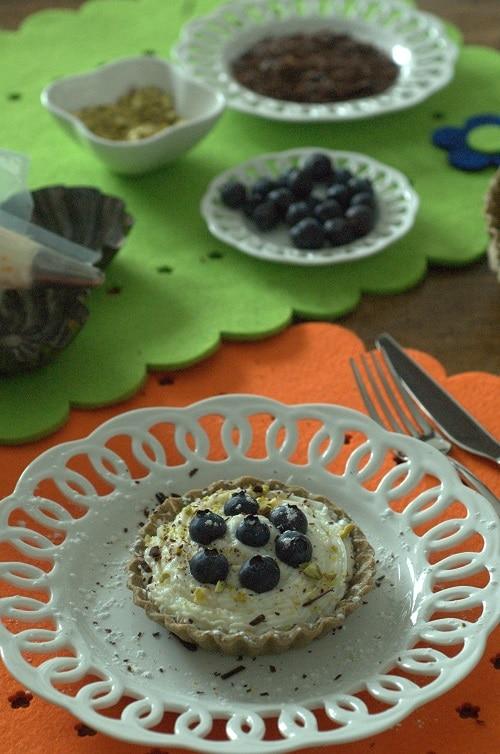Completare i cestini con l'aggiunta dei frutti di bosco, il cioccolato tagliato a scaglie sottili e i pistacchi tritati a mano.