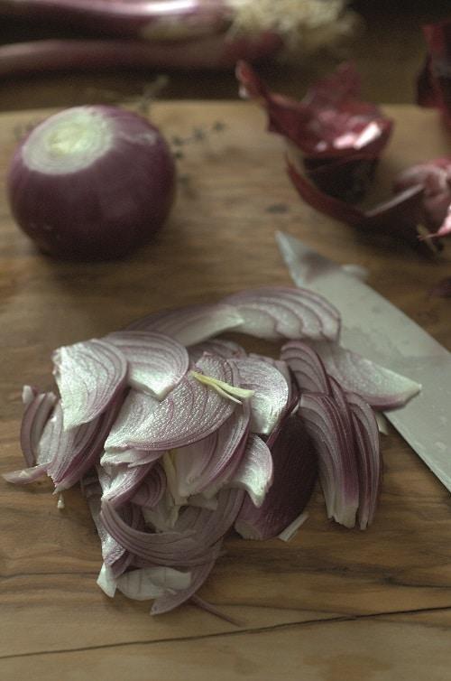 Tagliare le cipolle sottilmente, cuocerle per qualche minuto in una<br /> padella con un filo di olio extravergine d'oliva, unire un po' di vino bianco aromatico.