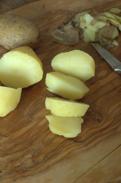 Per il cappuccino: lavare le patate e cuocerle in acqua senza sale, pelarle, schiacciarle, aggiungere il latte, lo zafferano, il sale e il pepe.