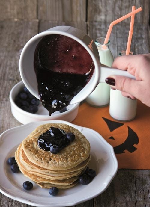 In un pentolino mettete 50 g di mirtilli insieme allo zucchero, allo sciroppo d'acero e all'acqua, far cuocere il tutto per 7-8 minuti a fiamma media fino a che lo zucchero non si sarà ben sciolto e aiutandosi con una forchetta per schiacciare i mirtilli. Servire i pancakes con lo sciroppo ottenuto ancora<br /> tiepido e i mirtilli freschi.