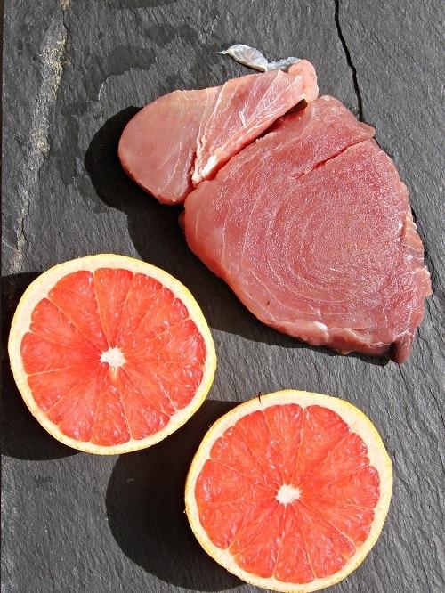 Sciacquare la melanzana dal sale e asciugarla,<br /> sporcare con 20 g di olio una placca da forno, disporvi<br /> le melanzane, mescolarle e poi allargarle; infornare il tutto a 180° per 10 minuti, fino a quando non risulteranno dorate.<br /> Preparare una salsa mescolando, con una frusta a fili, il succo del pompelmo con un cucchiaio di olio (10 g circa), un pizzico di sale, una macinata di pepe e le foglioline di maggiorana; emulsionare<br /> bene e tenere da parte.Poi spennellare la fetta di tonno con l'intingolo preparato e infornare a 200° per 10 minuti; sfornare e far intiepidire prima di tagliarlo a fettine sottili e successivamente ridurlo<br /> a striscioline.