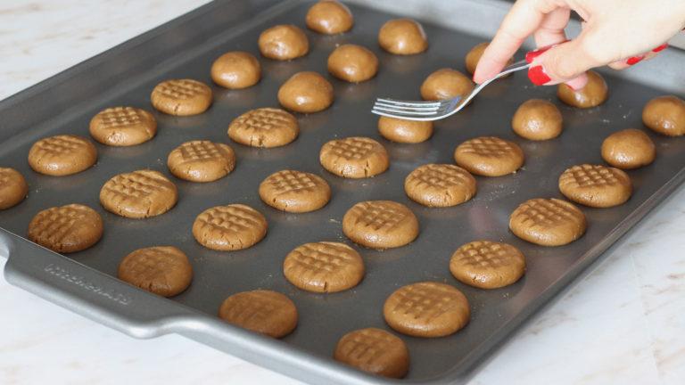 Trascorso il riposo dell'impasto, accendete il forno a 170°C. Preparate una teglia ampia ed iniziate a formare i biscotti: prelevate dall'impasto dei pezzi di circa 15 gr con cui formare delle palline leggermente schiacciate, che andrete via via ad adagiare nella teglia. Una volta formati tutti i biscotti, premeteli sopra delicatamente con i rebbi di una forchetta per formare una griglia decorativa.