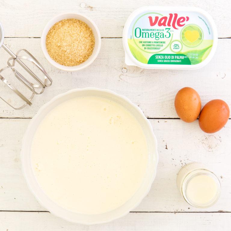 In una ciotola lavorare Vallè Omega3 con lo zucchero di canna e le uova fino a ottenere un composto liscio e omogeneo; a filo unire la bevanda all'avena al composto senza smettere di mescolare<br />