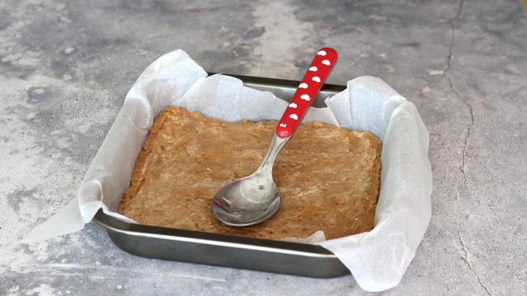 Mettete un terzo dell'impasto in frigo. Distribuite i restanti due terzi sul fondo di uno stampo quadrato da 18cm usando il dorso di un cucchiaio bagnato, fino a formare uno strato uniforme.